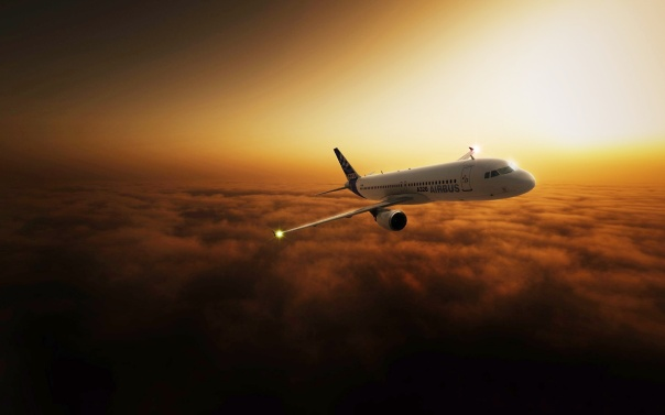 commercial_airline_plane_in_the_sky_after_sunset-wide