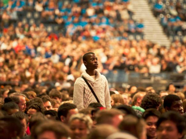Young-man-standing-in-a-seated-crowd_large